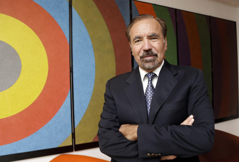 """In this Wednesday, Dec. 11, 2013 photo, developer and art collector Jorge Perez poses for a photograph in his office at the Related Group, in Miami. The artwork behind him is by artist Sol LeWitt and is titled """"Folding Screen 3 C-Arcs from the Midpoint of the Left Side."""" Perez, a major force behind Miami's urban development, donated a combined $40 million in cash and art, earning naming rights to the newly opened Perez Art Museum Miami. (AP Photo/Lynne Sladky)"""
