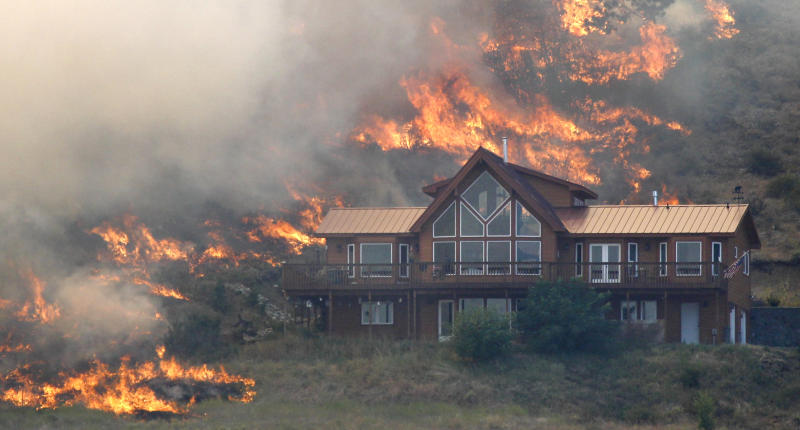 In this photo taken Tuesday, Aug. 14, 2012, flames surround a house on a hillside above Bettas Road near Cle Elum, Wash. A spokesman for the Washington state Department of Natural Resources said the house survived the fire because of the defensible space around the structure with the placement of the driveway and the lack of trees and brush up against the house, preventing flames from reaching it. Firefighters are still working to control the Bridge Taylor Fire and said that it's 25 percent contained. (AP Photo/Elaine Thompson)