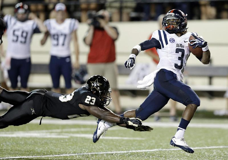 Mississippi running back Jeff Scott (3) avoids a tackle attempt by Vanderbilt defensive back Andre Hal (23) as Scott scores a touchdown on a 75-yard run with 1:07 left in the fourth quarter to give Mississippi a 39-35 win in an NCAA college football game on Friday, Aug. 30, 2013, in Nashville, Tenn. (AP Photo/Mark Humphrey)