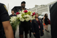 Miami Heat forward Udonis Haslem, carrying flowers, is accompanied by Miami-Dade County Mayor Daniella Levine Cava as he arrives to pay his respects at a makeshift memorial to the people who were killed and the scores who remain missing, nearly a week after the partial collapse of the Champlain Towers South condo building, Wednesday, June 30, 2021, in Surfside, Fla. (AP Photo/Gerald Herbert)