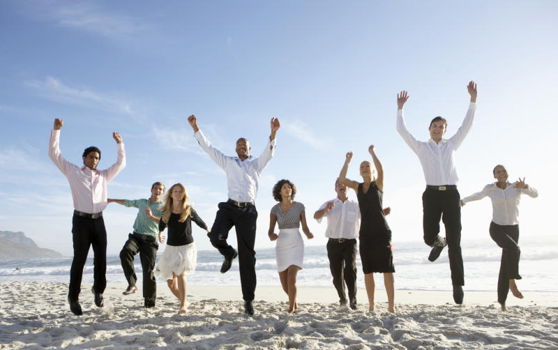 Men and women in professional attire jumping for joy on a beach.