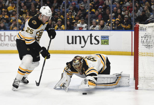 Boston Bruins goalie Tuukka Rask, right, reaches for a loose puck as the play is covered by defenseman Brandon Carlo (25) during the second period of an NHL hockey game against the Buffalo Sabres in Buffalo, N.Y., Saturday, Dec. 29, 2018. (AP Photo/Adrian Kraus)
