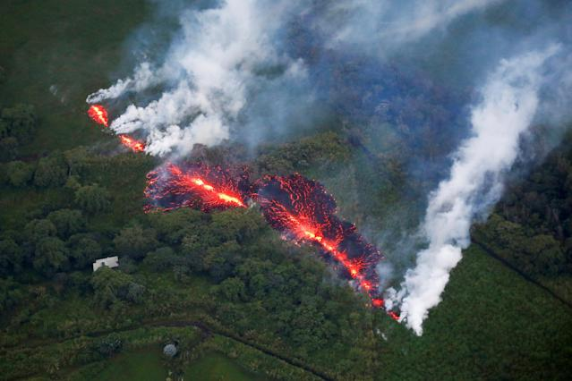 <p>Lava erupts from a fissure east of the Leilani Estates subdivision during ongoing eruptions of the Kilauea Volcano in Hawaii, on May 13, 2018. (Photo: Terray Sylvester/Reuters) </p>