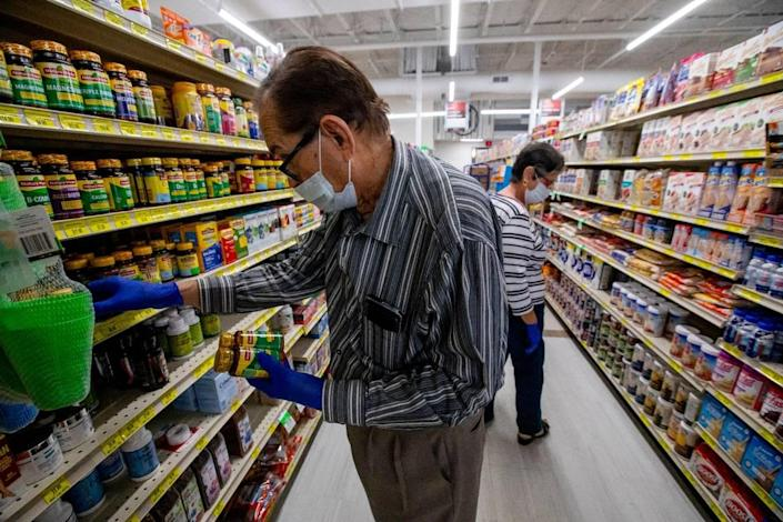 An older couple browses the vitamins at a Sedano's Supermarket in Hialeah, Florida on Wednesday, April 1, 2020.