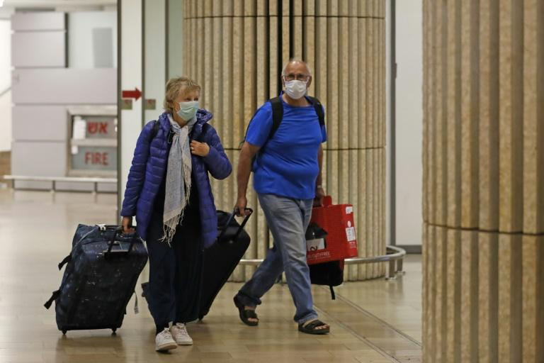 Passengers wearing protective masks in the arrival hall of Ben Gurion International Airport on Saturday