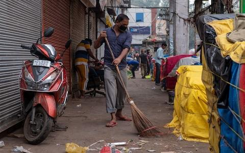 A man wearing a pollution mask sweeps a street with a broom in the old quarters of New Delhi  - Credit: LAURENE BECQUART/AFP via Getty Images