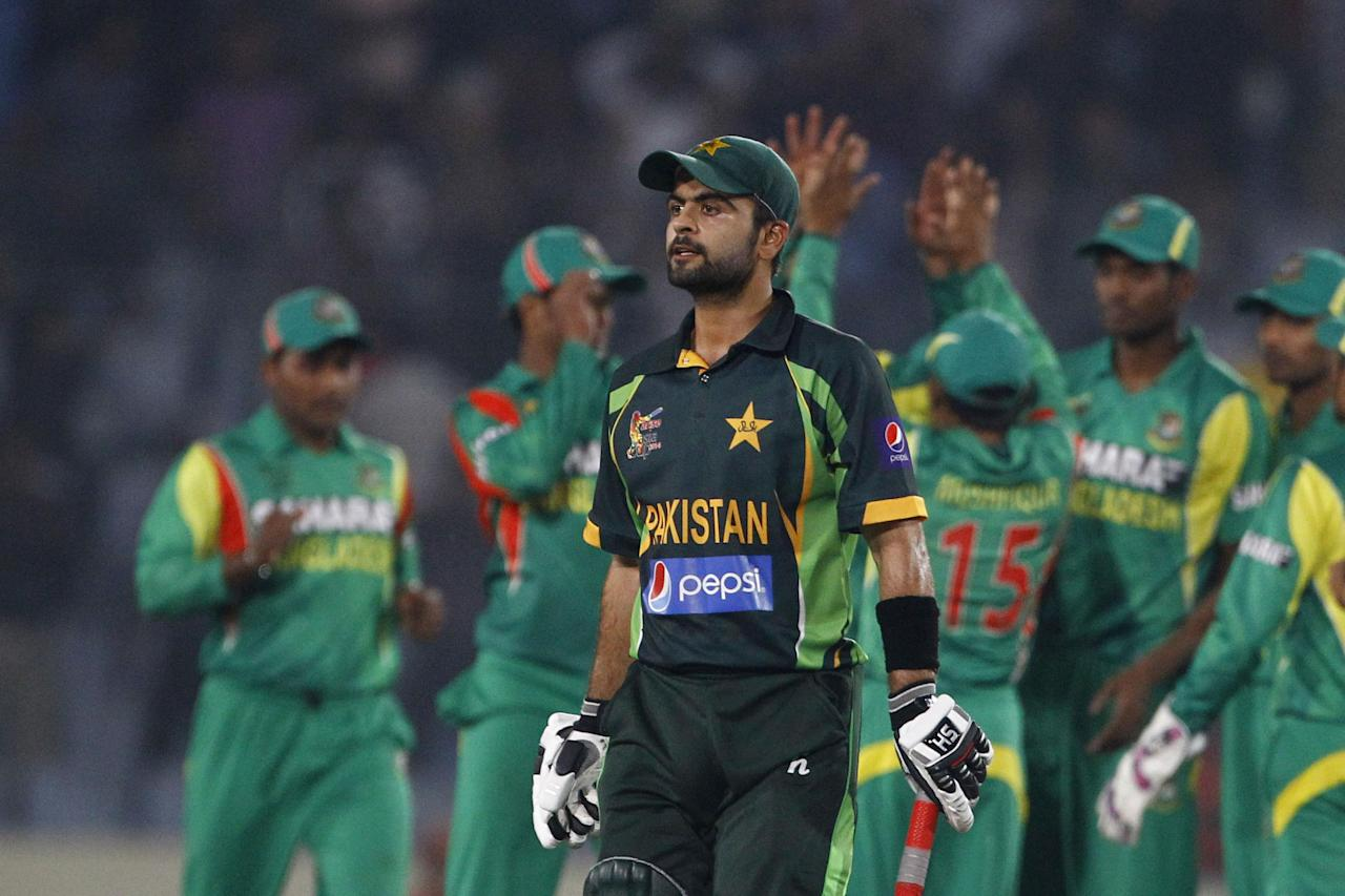 Pakistan's Ahmed Shehzad walks back to the pavilion after his dismissal by Bangladesh's Abdur Razzak during their match in the Asia Cup one-day international cricket tournament in Dhaka, Bangladesh, Tuesday, March 4, 2014. (AP Photo/A.M. Ahad)