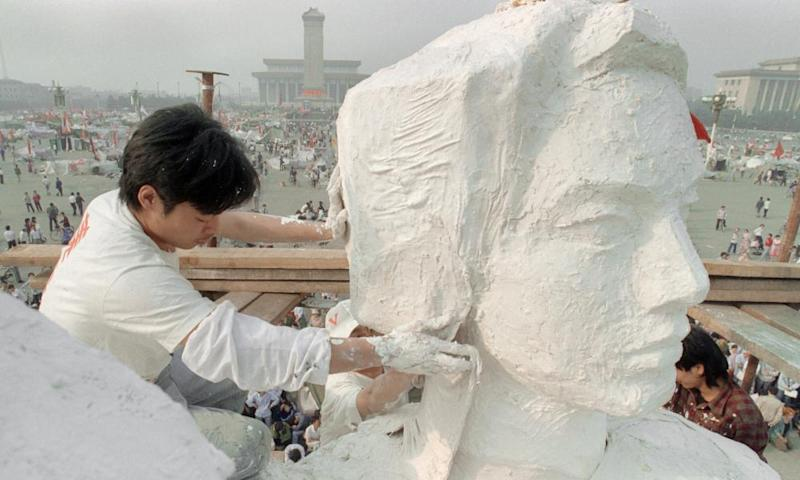 A student plasters the neck of the 'Goddess of Democracy', a replica of the Statue of Liberty, on 30 May 1989 in Tiananmen Square.