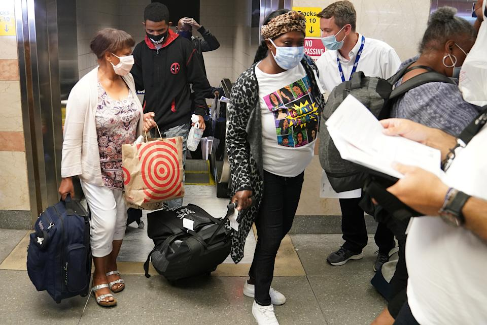 Passengers on a train from Florida mostly ignore workers at Penn Station during an effort to screen out-of-state travellers and enforce the state's 14-day coronavirus disease (COVID-19) quarantine in the Manhattan borough of New York City, New York, U.S., August 6, 2020. REUTERS/Carlo Allegri