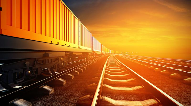 A freight train on the tracks as the sun sets