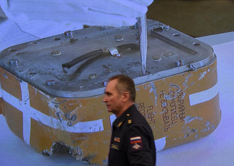 A Russian military official passes by a screen showing a live broadcast of the opening of the flight recorder from the Russian Sukhoi Su-24 bomber shot down by a Turkish jet on November 24, 2015 (AFP Photo/Vasily Maximov)