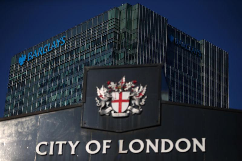 Barclays' building in Canary Wharf is seen behind a City of London sign outside Billingsgate Market in London