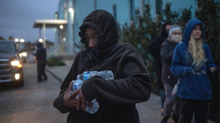 A woman carries bottled water she received from a shelter after record-breaking temperatures in Galveston, Texas, 18 February 2021