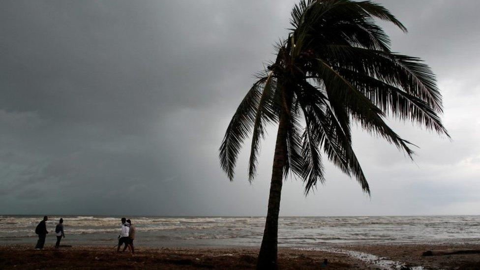 People walk along a beach after the passing of Hurricane Iota Nicaragua