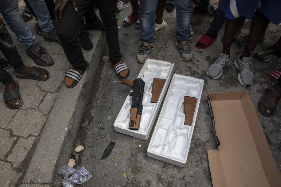 Protesters display toy guns used by musicians who were recording a music video the night before as they explain to journalists how police opened fire on the musicians killing one of them because police thought they were carrying real weapons, during a protest in downtown in Port-au-Prince, Haiti, Wednesday, Sept. 22, 2021. (AP Photo/Rodrigo Abd)