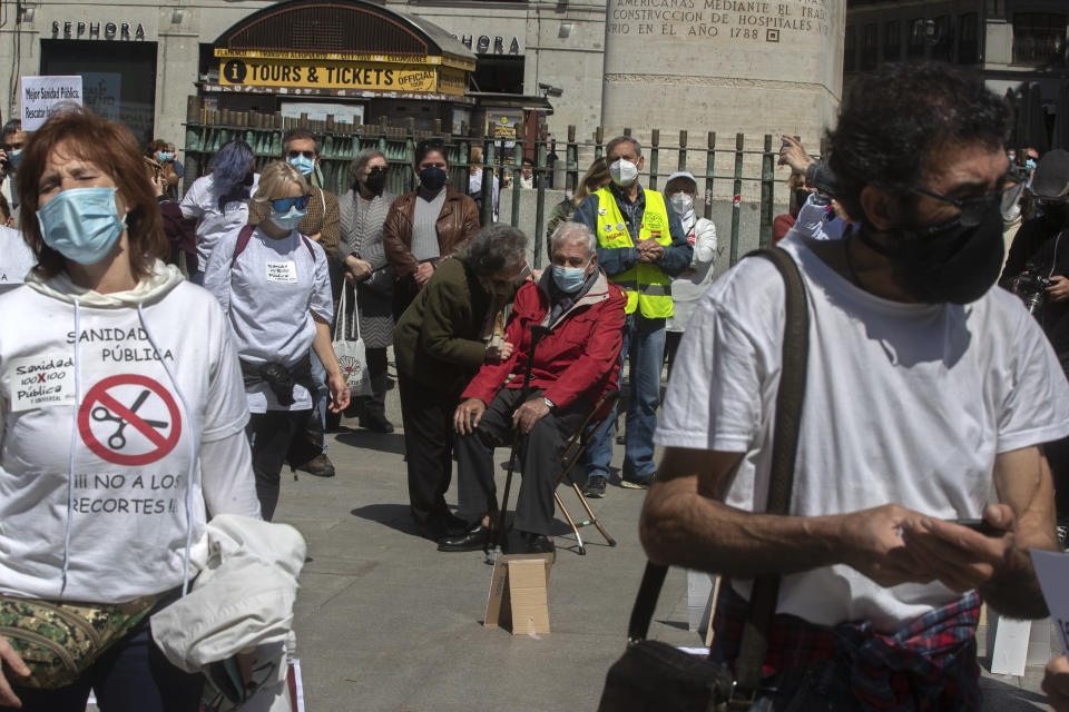 "A man sits down during a protest in the central Puerta del Sol to protect the national health service during and after the pandemic, in Madrid, Spain, Saturday, April 17, 2021. Spanish Prime Minister Pedro Sanchez says he is ""very hopeful"" that Spain can come up with its own COVID-19 vaccine by the end of the year. (AP Photo/Paul White)"