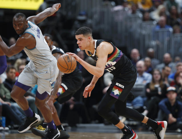 Denver Nuggets forward Michael Porter Jr., front picks up a loose ball as Charlotte Hornets center Bismack Biyombo watches during the second half of an NBA basketball game Wednesday, Jan. 15, 2020, in Denver. The Nuggets won 100-86. (AP Photo/David Zalubowski)