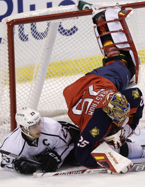 Los Angeles Kings right wing Dustin Brown (23) upends Florida Panthers goalie Jacob Markstrom (25) of Sweden, during the second period of an NHL hockey game, Sunday, Oct. 13, 2013, in Sunrise, Fla. (AP Photo/Wilfredo Lee)