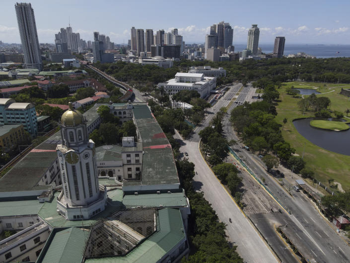 The Manila City Hall stands beside an almost empty road as the government implements a strict lockdown to prevent the spread of the coronavirus on Good Friday, April 2, 2021 in Quezon city, Philippines. Filipinos marked Jesus Christ's crucifixion Friday in one of the most solemn holidays in Asia's largest Catholic nation which combined with a weeklong coronavirus lockdown to empty Manila's streets of crowds and heavy traffic jams. Major highways and roads were eerily quiet on Good Friday and churches were deserted too after religious gatherings were prohibited in metropolitan Manila and four outlying provinces. (AP Photo/Aaron Favila)
