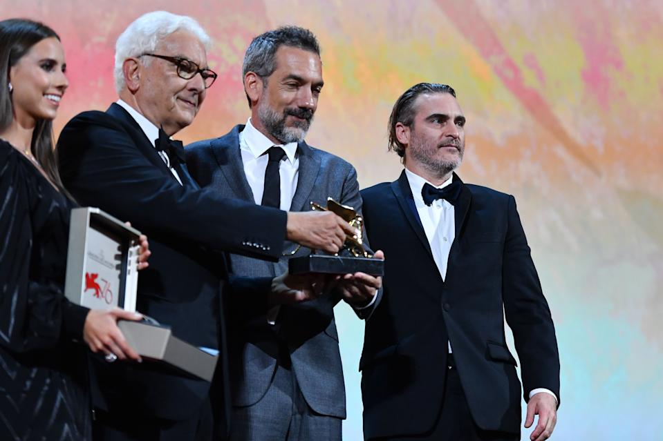 """US director Todd Phillips (C), flanked by US actor Joaquin Phoenix (R) and President of the Venice Biennale Paolo Baratta, holds the Golden Lion award for Best Film he received for the movie """"Joker"""" during the awards ceremony of the 76th Venice Film Festival on September 7, 2019 at Venice Lido. (Photo by Alberto PIZZOLI / AFP)        (Photo credit should read ALBERTO PIZZOLI/AFP/Getty Images)"""