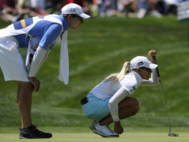 Pernilla Lindberg, of Sweden, and her caddy line up a putt on the first hole during the third round of the International Crown golf tournament on Saturday, July 26, 2014, in Owings Mills, Md.(AP Photo/Gail Burton)