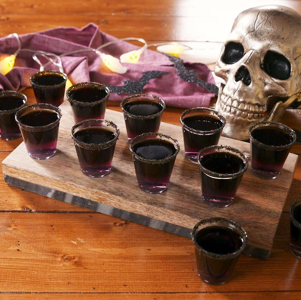 """<p>These shots are PERFECT for your next Halloween party—just make sure to give yourself plenty of time to prep them in advance. You want to make sure your purple layer is completely set before you pour the black layer on top. </p><p>Get the <a href=""""https://www.delish.com/uk/cocktails-drinks/a33978882/black-magic-jelly-shots-recipe/"""" rel=""""nofollow noopener"""" target=""""_blank"""" data-ylk=""""slk:Black Magic Jelly Shots"""" class=""""link rapid-noclick-resp"""">Black Magic Jelly Shots</a> recipe.</p>"""