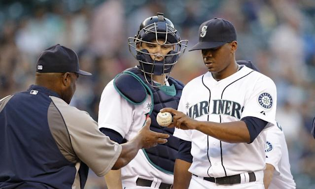 Seattle Mariners starting pitcher Roenis Elias, right, hands over the ball to manager Lloyd McClendon as catcher Mike Zunino watches during the fourth inning of a baseball game against the Minnesota Twins Wednesday, July 9, 2014, in Seattle. (AP Photo/Elaine Thompson)