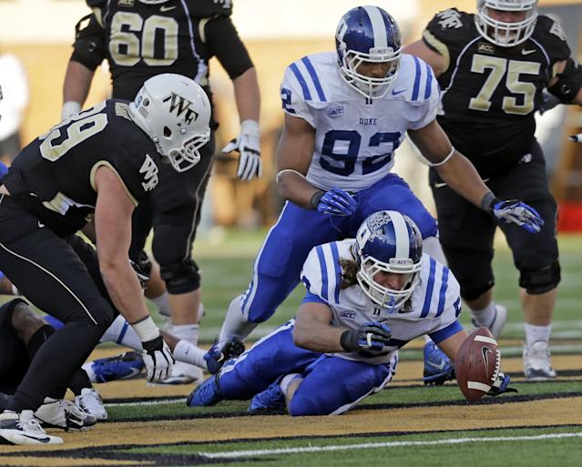 Duke linebacker Kelby Brown, bottom, recovers a fumble as Wake Forest tight end Spencer Bishop, left, and Justin Foxx, back, look on during the second half of an NCAA college football game in Winston-Salem, N.C., Saturday, Nov. 23, 2013. Duke won 28-21. (AP Photo/Chuck Burton)