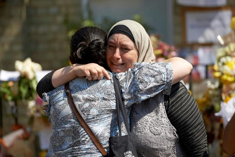 Women react after observing a minutes' silence in memory of the victims of the June 14 fire at the Grenfell Tower block, pictured on the horizon, in Kensington, west London, on June 19, 2017