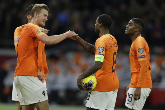 Netherlands' Matthijs de Ligt, left, celebrates with Netherlands' Georginio Wijnaldum, second right, after he scored his side's fourth goal during the Euro 2020 group C qualifying soccer match between The Netherlands and Estonia at the Johan Cruyff ArenA in Amsterdam, Netherlands, Tuesday, Nov. 19, 2019. (AP Photo/Peter Dejong)