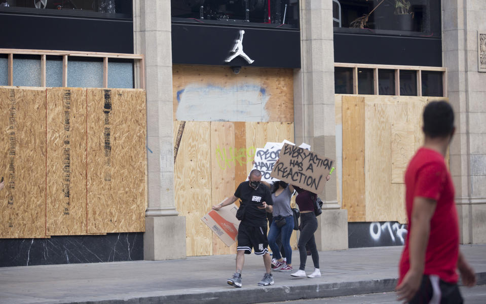 Protesters past by a NIKE store boarded up with a wood slabs as protests over the death of George Floyd continue Sunday, May 31, 2020, in Los Angeles. Armed National Guard soldiers lined the steps of Los Angeles City Hall, and cities across California declared curfews Sunday to head off more violence. (AP Photo/Ringo H.W. Chiu)
