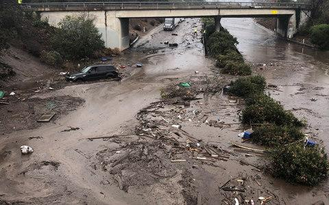 Abadoned cars stuck in flooded water on the freeway in Montecito - Credit: Reuters