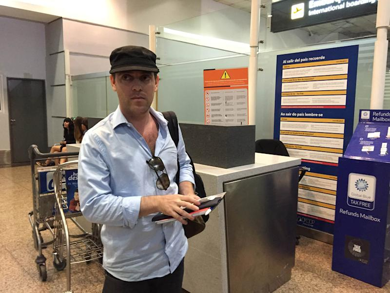 Argentine journalist Damian Pachter, who works for the Buenos Aires Herald newspaper, waits before taking a flight out of the country at Buenos Aires' airport