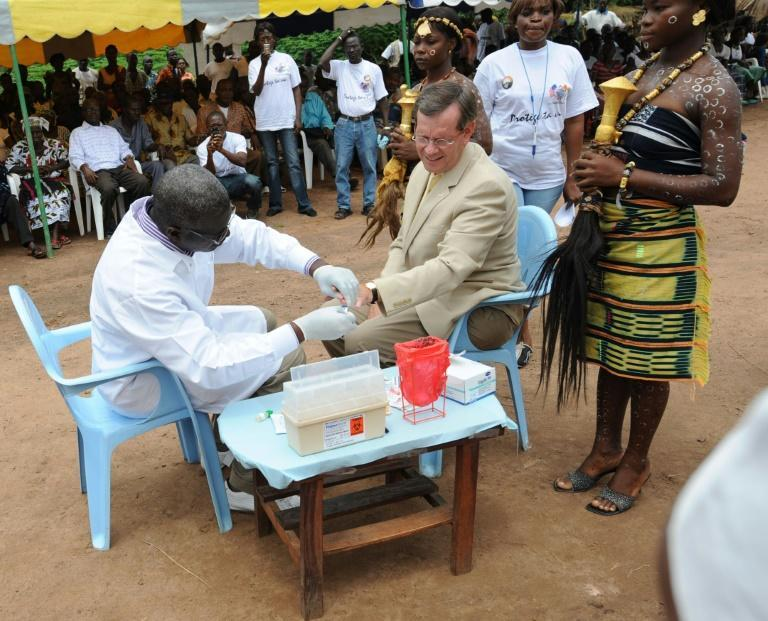 Then US health secretary Michael O.Leavitt (C) is given an AIDS-test in the village of Lomibo in Ivory Coast during a 2008 visit to organsations fighting HIV AIDS