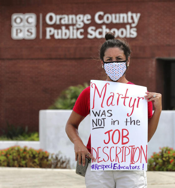 FILE - In this Tuesday, July 7, 2020 file photo, Rachel Bardes holds a sign in front of the Orange County Public Schools headquarters as teachers protest with a car parade around the administration center in downtown Orlando, Fla. As pressure mounts for teachers to return to their classrooms this fall, concerns about the pandemic are pushing many toward alternatives, including career changes, as some mobilize to delay school reopenings in areas hardest hit by the coronavirus. Teachers unions have begun pushing back on what they see as unnecessarily aggressive timetables for reopening. (Joe Burbank/Orlando Sentinel via AP, File)