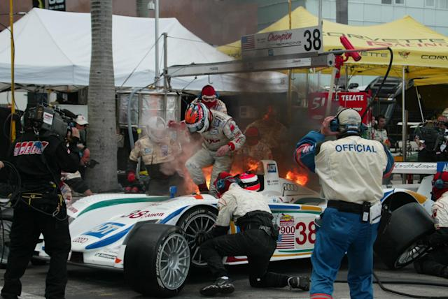 Driver JJ Lehto of Monaco jumps out of the #38 car as a flash fire erupts as he switches with fellow driver Johnny Herbert of England, (sitting in cockpit) during a pit stop during the American Le Mans Series race Saturday, Sept. 27, 2003, in Miami. The fire was extinguished and Herbert went on with the race. (AP Photo/Terry Renna)
