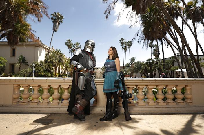 "Shawn Richter dressed as the Mandalorian and fiancée Lisa Lower as Cara Dune from the Disney+ series ""Star Wars: The Mandalorian"" at Balboa Park. Richter has been going to Comic-Con for 11 years. His outfit is partly handmade and 3D printed. Lower has been going to Comic-Con for seven years. The two do charity events in cosplay. <span class=""copyright"">(K.C. Alfred / The San Diego Union-Tribune)</span>"