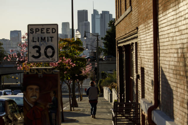 A pedestrian walks near Mariachi Plaza in Boyle Heights with the skyline of downtown Los Angeles on the horizon. (Photo: Patrick T. Fallon for Yahoo News)