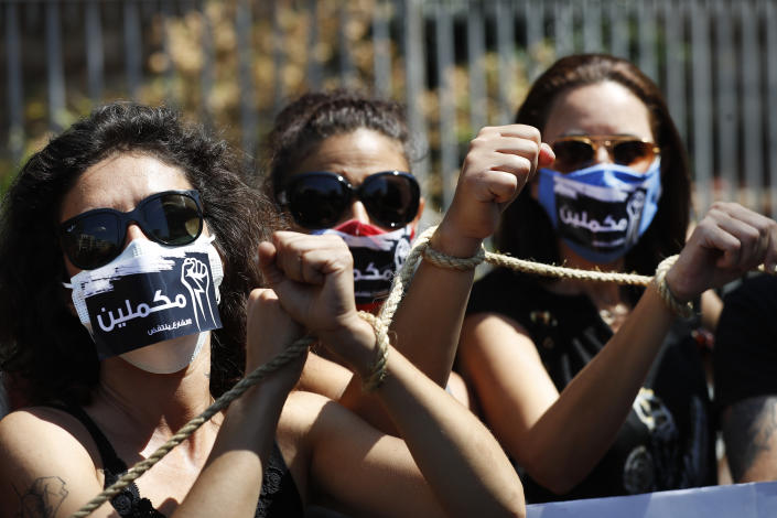 """Lebanese anti-government activists handcuff their hands by rope with Arabic stickers on their mouths that read:""""We will continue,"""" as they protest outside a Lebanese court demanding the improving judicial independence, in Beirut, Lebanon, Wednesday, June 17, 2020. A year after anti-government protests roiled Lebanon, dozens of protesters are being tried before military courts that human rights lawyers say grossly violate due process and fail to investigate allegations of torture and abuse. (AP Photo/Hussein Malla)"""