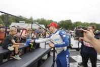 Alex Palou, center, celebrates by giving a child a signed cap after winning an IndyCar race at Road America in Elkhart Lake, Wisc., Sunday, June 20, 2021. (AP Photo/Jeffrey Phelps)