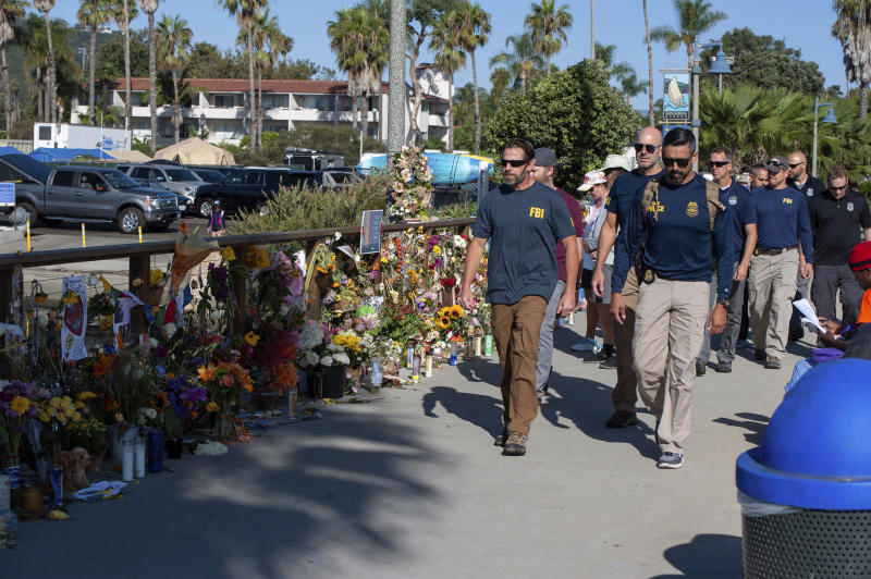 "FBI agents walk past a memorial for the victims of the Conception dive boat on the Santa Barbara Harbor, as authorities issue a search warrant for the Truth Aquatics' offices in Santa Barbara, Calif., Sunday, Sept. 8, 2019. The office was ringed in red ""crime scene"" tape as more than a dozen agents took photos and carried out boxes. Thirty-four people died when the Conception burned and sank before dawn on Sept. 2. They were sleeping in a cramped bunkroom below the main deck and their escape routes were blocked by fire. (AP Photo/Christian Monterrosa)"