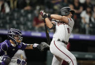 Arizona Diamondbacks' Josh Rojas, right, connects for a sacrifice fly to bring in a run off Colorado Rockies relief pitcher Jordan Sheffield in the eighth inning of a baseball game Friday, May 21, 2021, in Denver. (AP Photo/David Zalubowski)