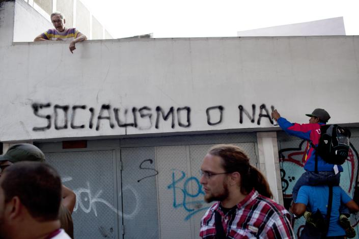 """A woman yells at members of a pro-government """"colectivo,"""" or """"collective,"""" writing graffiti on her home that reads in Spanish """"Socialism or nothing"""" in downtown Caracas, Venezuela, Thursday, Feb. 20, 2014. President Nicolas Maduro and his supporters say the escalating protests against his socialist government in the oil-rich but economically struggling country are part of an attempted coup sponsored by right-wing and """"fascist"""" opponents in Venezuela and abroad, particularly the United States. (AP Photo/Rodrigo Abd)"""