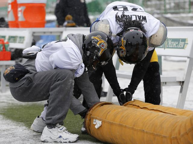 Hamilton Tiger-Cats' Brandon Banks (L) and Chevon Walker warm up their hands in the extreme cold during the team practice in Regina, Saskatchewan, November 20, 2013. The Saskatchewan Roughriders will play the Hamilton Tiger-Cats in the CFL's 101st Grey Cup in Regina November 24, 2013. REUTERS/Todd Korol (CANADA - Tags: SPORT FOOTBALL)
