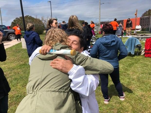 Mi'kmaq Elder Marlene Thomas, who survived the residential school in Shubenacadie, N.S., hugs a community member during the ceremony at Lennox Island on Monday.  (Brian Higgins/CBC - image credit)