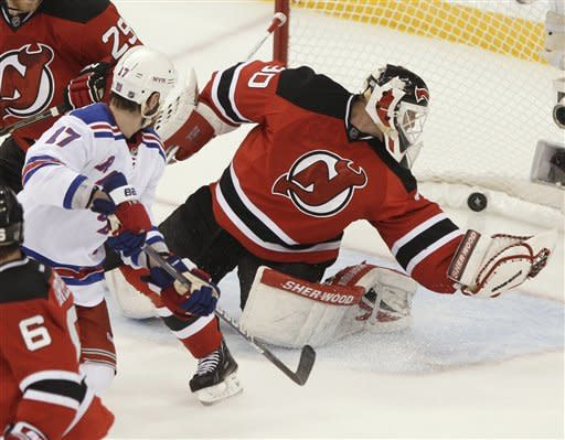 New York Rangers' Brandon Dubinsky, left, watches a shot by teammate Ryan Callahan go in for a goal past New Jersey Devils' Martin Brodeur during the second period of Game 6 of the NHL hockey Stanley Cup Eastern Conference finals Friday, May 25, 2012, in Newark, N.J. (AP Photo/Frank Franklin II)