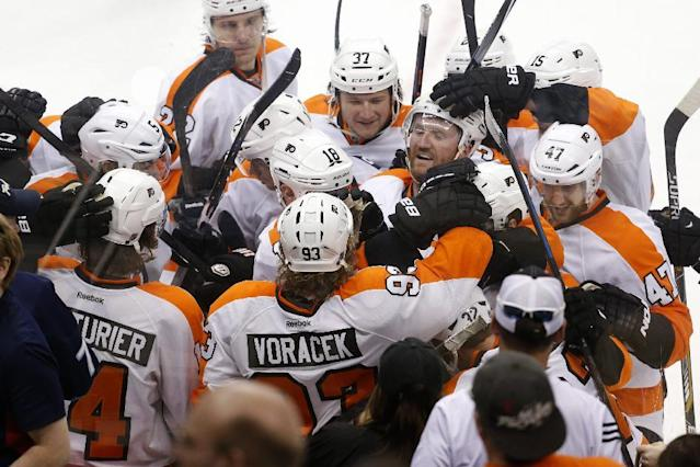 The Philadelphia Flyers celebrate after Philadelphia Flyers' Mark Streit (32) scored the game winning goal in overtime of an NHL hockey game against the Pittsburgh Penguins in Pittsburgh, Saturday, April 12, 2014. The Flyers won 4-3 in overtime. (AP Photo/Gene J. Puskar)