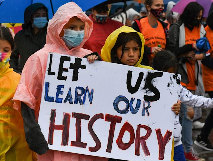 Eleven-year-olds Jaylee Fallis and L. In The Woods march during a demonstration through the streets of Pierre, S.D., on Sept. 13 after the final draft of the state's proposed social studies standards left out multiple specific references to the Oceti Sakowin.