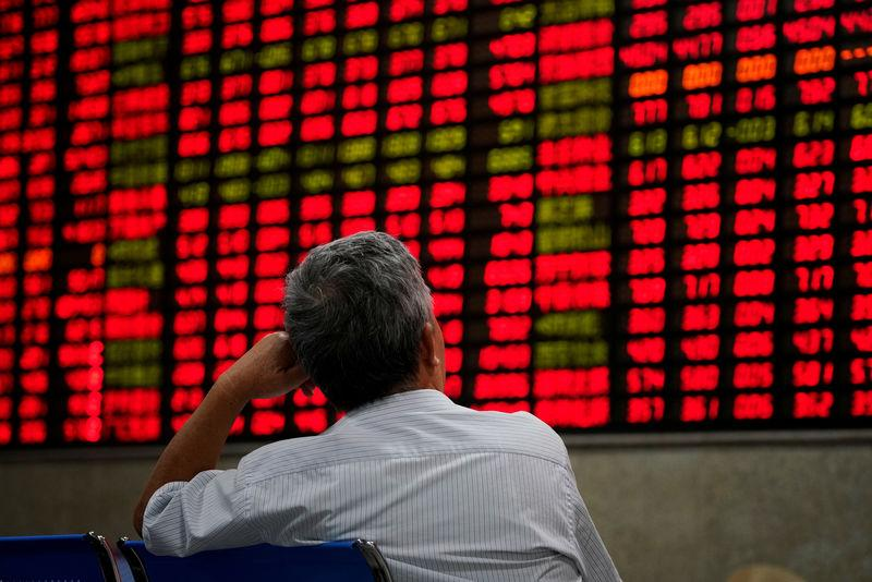 FILE PHOTO: FILE PHOTO: An investor looks at an electronic board showing stock information at a brokerage house in Shanghai, China September 7, 2018. REUTERS/Aly Song/File Photo