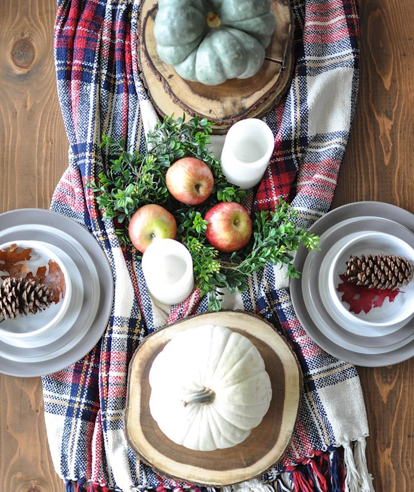"<p>When looking for a runner for her Thanksgiving table, Ashley Thurman from<a href=""https://cherishedbliss.com/a-simple-cozy-fall-tablescape/"" target=""_blank""> Cherished Bliss</a> pulled an unexpected home accessory to do the job: a fringed plaid blanket. Just as this blanket would warm up an armchair in the living room, placing it along the center of the table creates a cozy look. To complete the rustic-yet-modern style, large wood slices hold the pumpkins that serve as Thanksgiving centerpieces.</p>"